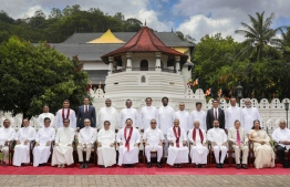 In this handout photograph released by the Sri Lankan President's Office on August 12 shows Sri Lanka's President Gotabaya Rajapaksa (front 7R) and Prime Minister brother Mahinda Rajapaksa (front 7L) along with cabinet ministers during a group photograph after the cabinet swearing-in ceremony at the Buddhist Temple of the Tooth in the ancient hill capital of Kandy, some 116 km from Colombo on August 12, 2020. - Sri Lanka president Gotabaya Rajapaksa retained the powerful defence portfolio and gave other key jobs to his close family in a 26-member cabinet appointed on August 12. (Photo by - / SRI LANKAN PRESIDENT'S OFFICE / AFP) /