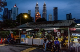 (FILES) In this file photo taken on June 4, 2020, people buy food at a shop, with the Petronas Twin Towers (C) seen in the night skyline of Kuala Lumpur. - Malaysia's economy suffered its worst contraction in more than 20 years during the second quarter, hit by a collapse in global trade and tough curbs to contain the coronavirus, the central bank said on August 14. (Photo by Mohd RASFAN / AFP)