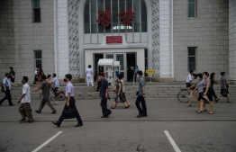 Pedestrians pass health screening booths at the entrance of the central Pyongyang Railway Station in Pyongyang on August 13, 2020. (Photo by KIM Won Jin / AFP)