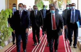"""A handout picture released by the Egyptian Prime Minister's official Facebook page on August 15, 2020 shows the mask-clad (COVID-19 coronavirus pandemic precaution) PM Mostafa Madbouli (L) being received by Sudan's PM Abdalla Hamdok (C-R) at the capital's Khartoum International Airport. (Photo by - / Egyptian Prime Minister's Office / AFP) / === RESTRICTED TO EDITORIAL USE - MANDATORY CREDIT """"AFP PHOTO / HO / EGYPTIAN PRIME MINISTER'S OFFICE""""- NO MARKETING NO ADVERTISING CAMPAIGNS - DISTRIBUTED AS A SERVICE TO CLIENTS =="""