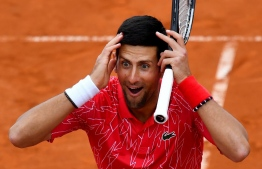 (FILES) In this file photo Serbia's Novak Djokovic reacts as he takes part in tennis match during a charity exhibition hosted by him, in Belgrade on June 12, 2020. - Novak Djokovic boosted the US Open by saying on August 13, 2020 he will play in the Grand Slam tennis event while reigning women's champion Bianca Andreescu joined a host of notable no-shows. Top-ranked Djokovic, a 17-time Slam singles champion, ended speculation by saying he would travel to New York on Saturday and play a tuneup event inside a COVID-19 quarantine bubble on the Flushing Meadows grounds ahead of the US Open start on August 31. (Photo by Andrej ISAKOVIC / AFP)
