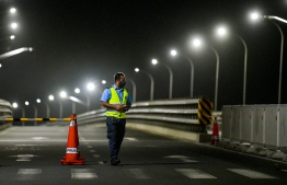 Covid-19/ VehiclesTraffic Police officer keeps watch in front of the Sinamale' Bridge: HPA reduced curfew hours and restrictions on vehicular movement to 2300 to 0400 hrs. PHOTO: AHMED AWSHAN ILYAS / MIHAARU