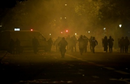 French anti-riot policemen walk in tear gas smokes as they escort Paris Saint-Germain (PSG) supporters around the Parc des Princes stadium on August 23, 2020, after the UEFA Champions League final football match between PSG and Bayern Munich played at the Luz stadium in Lisbon. (Photo by Alain JOCARD / AFP)