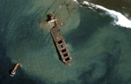 This August 18, 2020, handout satellite image obtained courtesy of Maxar Technologies shows a close up view of the MV Wahashio shipwreck and tugs being towed away from the reef off the coast of Mauritius. Handout / Satellite image ©2020 Maxar Technologies / AFP