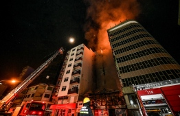 Maldives National Defence Force (MNDF) and Maldives Airports Company Limited (MACL)'s firefighters attempting to control the blaze engulfing the top floors of Gadhage Mohamed Fulhu Building, where Ooredoo Maldives' headquarters are located. PHOTO: NISHAN ALI/ MIHAARU