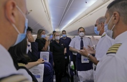 A picture taken on August 31, 2020, shows a member of the flight crew speaking while on board the El Al's airliner, ahead of the first-ever commercial flight from Israel to the UAE at the Ben Gurion Airport near Tel Aviv, which will carry a US-Israeli delegation to the UAE following a normalisation accord. (Photo by NIR ELIAS / POOL / AFP)