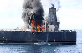 This handout photograph taken on September 3, 2020, and released by Sri Lanka's Air Force, shows black smoke coming out from the Panamanian-registered crude oil tanker New Diamond, some 60 km off Sri Lanka's eastern coast. (Photo by - / Sri Lankan Air Force / AFP) /