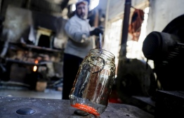 A glassblower forms glass at factory, which is recycling the broken glass as a result of the Beirut explosion, in the northern Lebanese port city of Tripoli on August 25, 2020. - The August 4 port explosion ripped through countless glass doors and windows when it laid waste to whole Beirut neighbourhoods, killing at least 190 people and wounding thousands more. Volunteers, non-governmental groups and entrepreneurs salvaged a fraction of the tonnes of broken glass that littered the streets, some of it through recycling at Wissam Hammoud's family's glass factory. (Photo by JOSEPH EID / AFP)