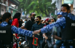 Police holding back opposition protesters in a rally held in Male' City. PHOTO: MIHAARU