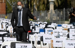 """Catalan regional president Quim Torra walks among chairs representing the number of lawsuits against separatists in front of the Arc de Triomf in Barcelona on September 11, 2020 marking the """"Diada"""", national day of Catalonia. - Like every September 11 since 2012, Catalan separatists want to mobilize to defend secession from the rest of Spain, but the ranks could be sparse both because of the pandemic and by divisions within the political movement. PHOTO: JOSEP LAGO / AFP"""