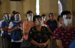 In this photo taken on September 2, 2020, Catholics wearing face shields queue up to receive communion during a mass inside a church in Manila. - Many face the new normal in the Philippines, where it is now compulsory to wear both face masks and plastic shields in indoor public spaces and on public transport to curb the spread of the COVID-19 coronavirus. (Photo by Ted ALJIBE / AFP) /
