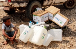 A child waits next to jerry cans and aid packages as Yemenis displaced by conflict receive huamnitarian aid provided by the Abs Development Organisation (ADO) in the northern province of Hajjah on September 17, 2020. (Photo by ESSA AHMED / AFP)