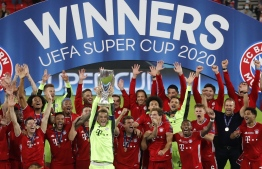 Bayern Munich's German goalkeeper Manuel Neuer and his teammates celebrate with the trophy after the UEFA Super Cup football match between FC Bayern Munich and Sevilla FC at the Puskas Arena in Budapest, Hungary on September 24, 2020. (Photo by BERNADETT SZABO / POOL / AFP)