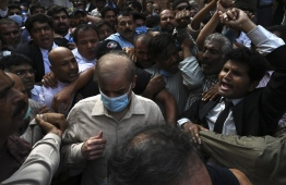 Shahbaz Sharif (C wearing mask), Pakistani opposition leader and brother of former prime minister Nawaz Sharif, comes out from the high court surrounded by supporters after the court rejected his bail plea in a money laundering and assets beyond income case, in Lahore on September 28, 2020. - Pakistani anti-corruption officials arrested the country's opposition leader Shahbaz Sharif on September 28, days after he vowed to help lead efforts to dislodge Prime Minister Imran Khan's government. (Photo by Arif ALI / AFP)
