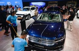Two staffs clean a Volkswagen New Phideon car at the Beijing Auto Show in Beijing on September 26, 2020. (Photo by WANG Zhao / AFP)