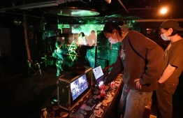 This picture taken on September 26, 2020 shows staffs checking for online broadcast of a farewell party of the underground music club MWG in the Hongdae nightlife district of Seoul as the club shuts down due to the COVID-19 coronavirus pandemic. - Tucked away in the dazzling neon of Seoul's Hongdae nightlife district, Club MWG used to be the area's oldest-running underground clubs -- until it became one of the latest victims of the coronavirus pandemic. (Photo by Jung Yeon-je / AFP)