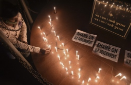 A member of the National Students' Union of India (NSUI) places a candle besides placards after a candlelight vigil following accusations of Indian Police forcibly cremating the body of a 19-year-old woman victim, who was allegedly gang-raped by four men in Bool Garhi village of Uttar Pradesh state, in Ahmedabad on September 30, 2020. - Indian police were accused on September 30 of forcibly cremating the body of a 19-year-old alleged gang-rape victim as anger grew over the latest horrific sexual assault to rock the country. The teenager from India's marginalised Dalit community suffered serious injuries in a brutal sexual attack two weeks ago, according to her family and police, and died at a New Delhi hospital on September 29. (Photo by SAM PANTHAKY / AFP)