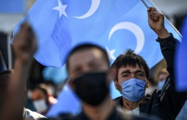 Supporters of China's Muslim Uighur minority wave flags of East Turkestan and hold placards as they gather at the Beyazid square on October 1, 2020 during a demonstration to protest China's Uighur treatment in Istanbul. (Photo by Ozan KOSE / AFP)