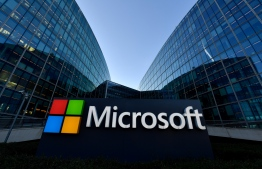 (FILES) In this file photo taken on March 5, 2018 the logo of French headquarters of American multinational technology company Microsoft, is pictured in Issy-Les-Moulineaux, a Paris suburb. - Software giant Microsoft will let employees work from home permanently if they choose to, US media reported on October 9, 2020, becoming the latest employer to expand work-from-home provisions prompted by the Covid-19 pandemic. (Photo by GERARD JULIEN / AFP)