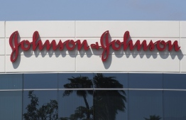 (FILES) In this file photo taken on August 28, 2019 a sign on a building at the Johnson & Johnson campus shows their logo in Irvine, California. - Johnson & Johnson said October 12, 2020, it had temporarily halted its Covid-19 vaccine trial because one of its participants had become sick. (Photo by Mark RALSTON / AFP)