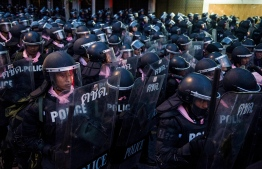 Riot police walk to disperse pro-democracy protesters in Bangkok on October 15, 2020, after Thailand issued an emergency decree following an anti-government rally the previous day. (Photo by STR / AFP)