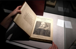 An employee holds a copy of the first collection of plays by William Shakespeare. PHOTO: REUTERS
