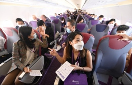 "Staff members from budget carrier HK Express take part in a preview ""Flycation"" flight around Hong Kong on October 15, 2020, during an inaugural ""flight to nowhere"" journey filled with media and staff, sparking criticism from environmentalists. (Photo by PETER PARKS / AFP)"