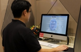 This photo taken on October 1, 2020 shows a staff member of government technology agency GovTech demonstrating the use of facial verification technology to access government services on a computer at a community centre in Singapore. - Singapore will become the world's first country to use facial verification in its national ID scheme, but privacy advocates are alarmed by what they say is an intrusive system vulnerable to abuse. (Photo by MARTIN ABBUGAO / AFP) /