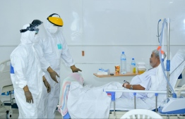 Healthcare workers in PPE attending to an elderly man that tested COVID positive: There has been 20 COVID-19 fatalities in May -- Photo: Nishan Ali/ Mihaaru