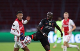 Ajax's Moroccan defender Noussair Mazraoui (L) vies for the ball with Liverpool's Senegalese forward Sadio Mane during the UEFA Champions League Group D first-leg football match between Ajax Amsterdam and Liverpool FC at the Johan Cruijff Arena in Amsterdam on October 21, 2020. (Photo by Kenzo Tribouillard / AFP)