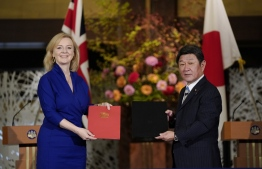 British Secretary of State for International Trade Elizabeth Truss (L) and Japanese Foreign Minister Toshimitsu Motegi exchange documents during a signing ceremony for economic partnership between Japan and Britain at the Iikura Annex of the Foreign Ministry in Tokyo on October 23, 2020. (Photo by Kimimasa MAYAMA / POOL / AFP)