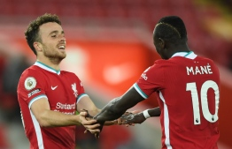 Liverpool's Portuguese striker Diogo Jota (L) celebrates scoring their second goal with Liverpool's Senegalese striker Sadio Mane (R) during the English Premier League football match between Liverpool and Sheffield United at Anfield in Liverpool, north west England on October 24, 2020. (Photo by Stu Forster / POOL / AFP)
