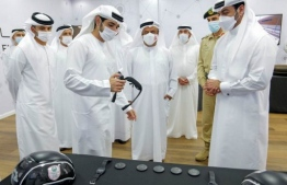 "A handout image provided by United Arab Emirates News Agency (WAM) shows Crown Prince of Dubai Sheikh Hamdan Bin Mohammed bin Rashid Al Maktoum (2nd L) and Sheikh Mansour bin Mohammed bin Rashid al Maktoum (L) during the opening of the smart simulation training station in the Gulf emirate, on October 25, 2020. - Dubai, which sees itself as a leading ""smart city"" in the Middle East, has ambitions to become a hub for technology and artificial intelligence. Both sectors will be on show when it opens the multi-billion-dollar Expo fair. (Photo by - / WAM / AFP) /"