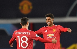 Manchester United's English striker Marcus Rashford (R) celebrates scoring his team's third goal, his second, with Manchester United's Portuguese midfielder Bruno Fernandes, during the UEFA Champions league group H football match between Manchester United and RB Leipzig at Old Trafford stadium in Manchester, north west England, on October 28, 2020. (Photo by Anthony Devlin / AFP)
