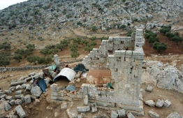 An aerial view shows the tents of war-displaced Syrians living amid Roman ruins on November 1, 2020 at the UNESCO-listed site of Baqirha not far from the Turkish border, in a region of northwest Syria filled with abandoned Roman and Byzantine settlements. - Almost one million Syrians fled their homes last winter during a Russia-backed offensive on Syria's last rebel stronghold of Idlib, and dozens of them have settled in the UNESCO-listed site of Baqirha, near the Turkish border, among centuries-old Roman and Byzantine ruins. (Photo by Abdulaziz ketaz / AFP)