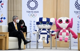 International Olympic Committee (IOC) president Thomas Bach sits next to Tokyo 2020 Olympic and Paralympic Games's mascots during a meeting with Tokyo governor in Tokyo on November 16, 2020. (Photo by CHARLY TRIBALLEAU / AFP)