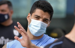 (FILES) In this file picture taken on November 12, 2020 Uruguay's Luis Suarez waves to supporters before a training session in Barranquilla, Colombia, on the eve of a 2022 FIFA World Cup South American qualifier football match against Colombia, amid the COVID-19 coronavirus pandemic. - Suarez tested positive for the novel coronavirus COVID-19, the Uruguayan Football Association informed on November 16, 2020. He will miss the 2022 FIFA World Cup South American qualifier football match against Brazil at home on November 17. The Atletico de Madrid striker will also miss the Spanish La Liga match against ex-team Barcelona on November 21. (Photo by Raul ARBOLEDA / AFP)