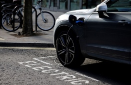"A charging cable is pictured plugged into a Volvo electric vehicle (EV), parked in a parking bay reserved for electric vehicles, in London on November 18, 2020. Britain will ban petrol and diesel vehicle sales from 2030 as part of a 10-point plan for a ""green industrial revolution"" to be unveiled Wednesday by Prime Minister Boris Johnson. The British premier has earmarked £12 billion (13.4 billion euros, $15.9 billion) for the wide-ranging plans, which he hopes will secure up to 250,000 jobs and help meet a target for the UK to become carbon neutral by 2050. Tolga Akmen / AFP"
