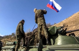 This handout picture released by the Russian Defence Ministry on November 13, 2020 shows two soldiers attaching a flag on the Russian peacekeeping forces military vehicle as they move on the road towards Martuni. - Russian peacekeepers began deploying in Karabakh on November 11 as part of the terms of the accord and took control of a key transport artery connecting Armenia to the disputed province. Russian military officials said the mission consisting of nearly 2,000 troops would put in place 16 observation posts in mountainous Nagorno-Karabakh and along the Lachin corridor. (Photo by Handout / Russian Defence Ministry / AFP) /