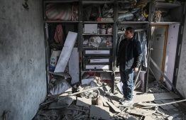 A man inspects a damaged house after several rockets land at Khair Khana, north west of Kabul on November 21, 2020. - A series of loud explosions shook central Kabul on November 21, including several rockets that landed near the heavily fortified Green Zone where many embassies and international firms are based, officials said. (Photo by WAKIL KOHSAR / AFP)