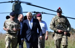 (FILES) In this file photo taken on September 19, 2019, Britain's Prime Minister Boris Johnson (C) arrives with Britain's Defence Secretary Ben Wallace (2L) to visit military personnel on Salisbury plain training area near Salisbury, south-west England. - Prime Minister Boris Johnson will on Thursday, November 19, unveil what is being billed as Britain's biggest programme of investment in the armed forces since the end of the Cold War. (Photo by Ben STANSALL / POOL / AFP)