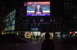 People walk below a giant screen showing news coverage of China's President Xi Jinping's speech via a virtual meeting to the Asia-Pacific Economic Cooperation (APEC) forum in Malaysia, outside a shopping mall in Beijing on November 19, 2020. (Photo by GREG BAKER / AFP)