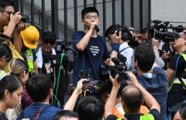 (FILES) In this file photo taken on June 21, 2019, pro-democracy activist Joshua Wong (C) speaks to protesters outside the police headquarters in Hong Kong. - Prominent Hong Kong dissident Joshua Wong announced he and two other leading activists will plead guilty at the opening of a trial over their involvement in last year's protests on November 23, 2020, adding he expects to be jailed. (Photo by ANTHONY WALLACE / AFP)