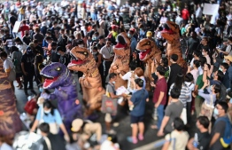 This photo taken with a tilt-shift lens shows protesters dressed in dinosaur costumes -- which pro-democracy activists said represents the older generation of Thai politicians -- during a 'Bad Student' rally in Bangkok on November 21, 2020. (Photo by Mladen ANTONOV / AFP)