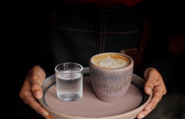 A barista at Meraki carries a tray with a cup of specialty coffee. PHOTO: BIG 7 TRAVEL GUIDE