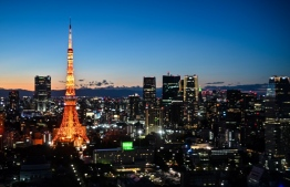 The Tokyo Tower is seen at dusk in the Japanese capital on November 28, 2020. (Photo by CHARLY TRIBALLEAU / AFP)
