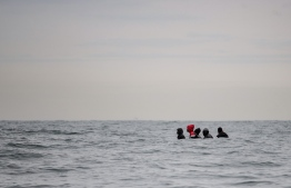 Migrants sit onboard a boat navigating in agitated waters between Sangatte and Cap Blanc-Nez (Cape White Nose), in the English Channel off the coast of northern France, as they attempt to cross the maritime borders between France and the United Kingdom on August 27, 2020. - The number of migrants crossing the English Channel -- which is 33,8 km (21 miles) at the closest point in the Straits of Dover -- in small inflatable boats has spiralled over the summer of the 2020. According to authorities in northern France some 6,200 migrants have attempted the crossing between January 1 and August 31, 2020, compared with 2,294 migrants for the whole of 2019. (Photo by Sameer Al-DOUMY / AFP)  Migrants sit onboard a boat navigating in agitated waters between Sangatte and Cap Blanc-Nez (Cape White Nose), in the English Channel off the coast of northern France, as they attempt to cross the maritime borders between France and the United Kingdom on August 27, 2020. (Photo by Sameer Al-DOUMY / AFP)