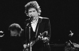 "Still breakin' records: Bob Dylan Bob closed a historic deal involving hundreds of his originals for a whopping nine figures on Monday in an agreement that has been described as ""one of the most important"" in music publishing, of all time. Photographed above, Dylan performs in February of 1974, alongside The Band at Los Angeles' the Forum venue. PHOTO: STAR TRIBUNE / TRIB LIVE / AP"