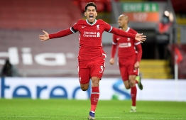 Liverpool's Brazilian midfielder Roberto Firmino celebrates scoring his team's second goal during the English Premier League football match between Liverpool and Tottenham Hotspur at Anfield in Liverpool, north west England on December 16, 2020. - Liverpool won the match 2-1. (Photo by PETER POWELL / POOL / AFP) / RESTRICTED TO EDITORIAL USE. No use with unauthorized audio, video, data, fixture lists, club/league logos or 'live' services. Online in-match use limited to 120 images. An additional 40 images may be used in extra time. No video emulation. Social media in-match use limited to 120 images. An additional 40 images may be used in extra time. No use in betting publications, games or single club/league/player publications. /