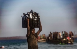 A fisherman balances a crate of fishes on his head on December 9, 2020 outside on the coast of the Paquitequete district of Pemba where internal displaced people are fleeing from unrest in the norther part of the Cabo Delgado area in Mozambique. (Photo by Alfredo Zuniga / AFP)